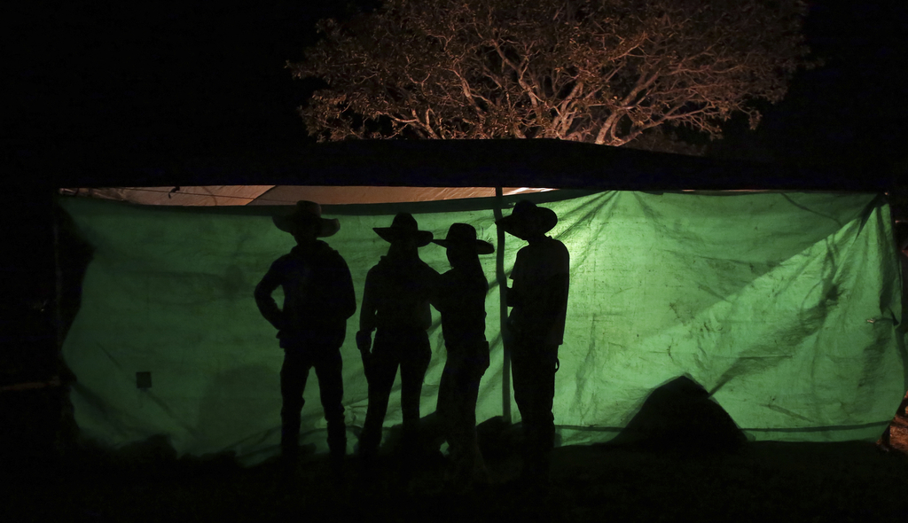 In this July 20, 2017 photo, youths talk during the night before the trip to the Serra da Boa Vista, during the Ox Cart Festival in Vazante, Minas Ger...