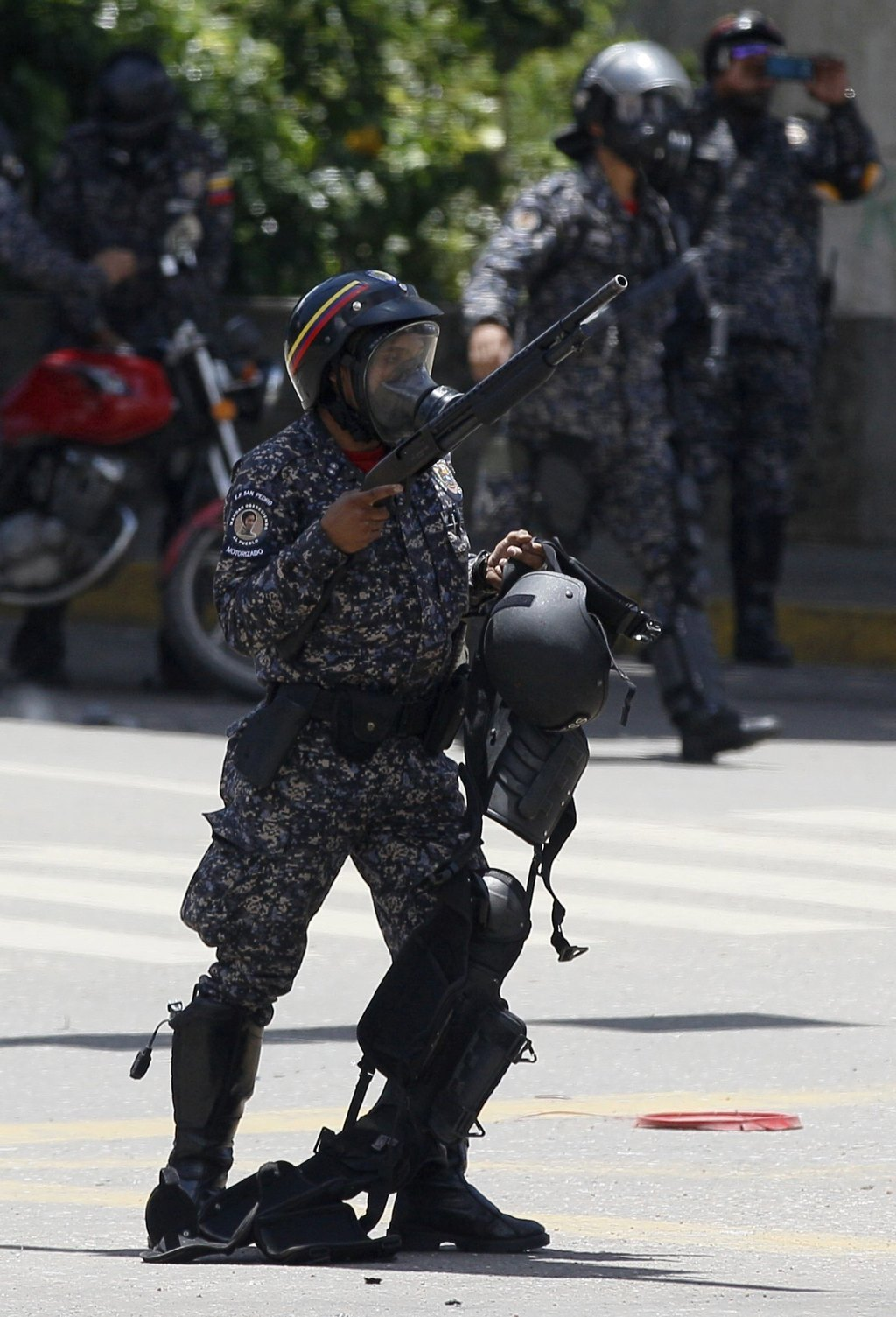 A Venezuelan Bolivarian National police officer carries the web gear of a fellow officer that was injured by an explosion at Altamira square during cl...