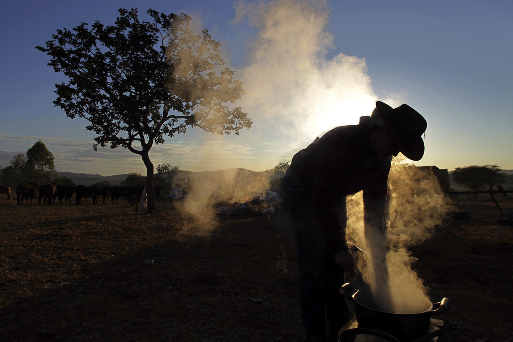 In this July 21, 2017 photo, a woman prepares breakfast on the camp fire at sunrise, before the ascent to the Serra da Boa Vista, during Ox Cart Festi...