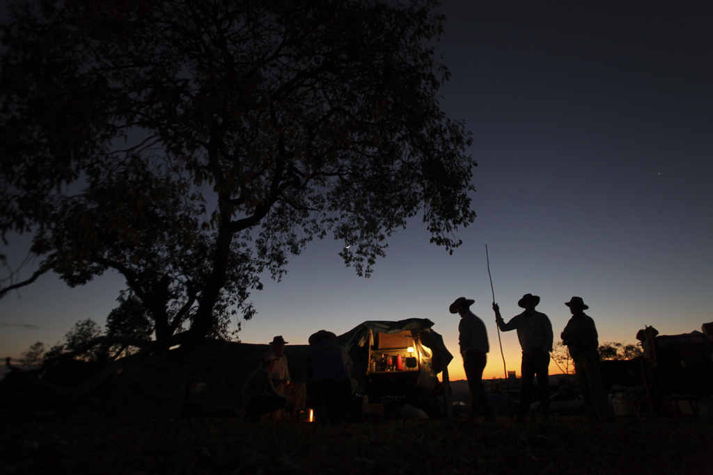 In this July 21, 2017 photo, cowboys have a chat at sunrise, before the ascent of the Serra da Boa Vista, during the Ox Cart Festival in Vazante, Mina...