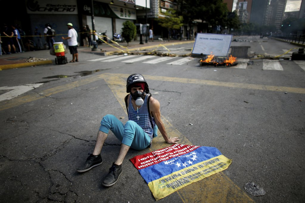 An anti-government demonstrator rests on the ground near a barricade in Caracas, Venezuela, Sunday, July 30, 2017. Venezuelans appear to be abstaining...