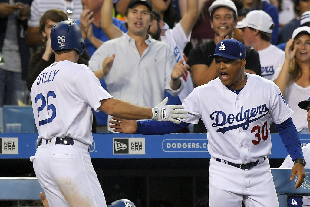 Los Angeles Dodgers' Chase Utley, left, is congratulated by manager Dave Roberts after scoring on a single by Yasiel Puig during the ninth inning of a...