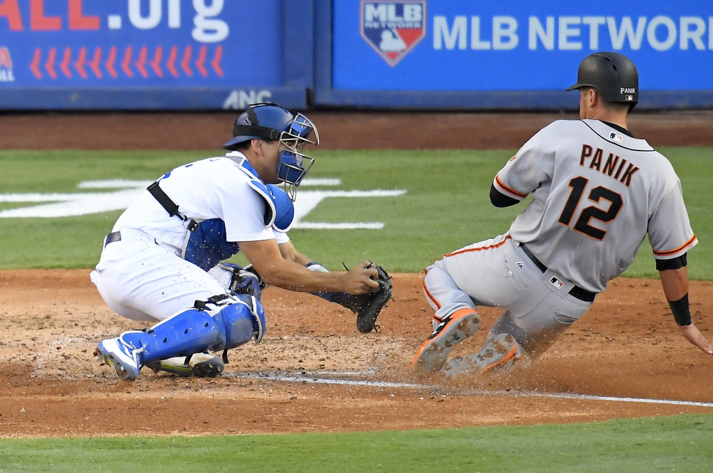 Los Angeles Dodgers catcher Austin Barnes, left, gets set to tag out San Francisco Giants' Joe Panik as he tries to score on a fly ball hit by Brandon...