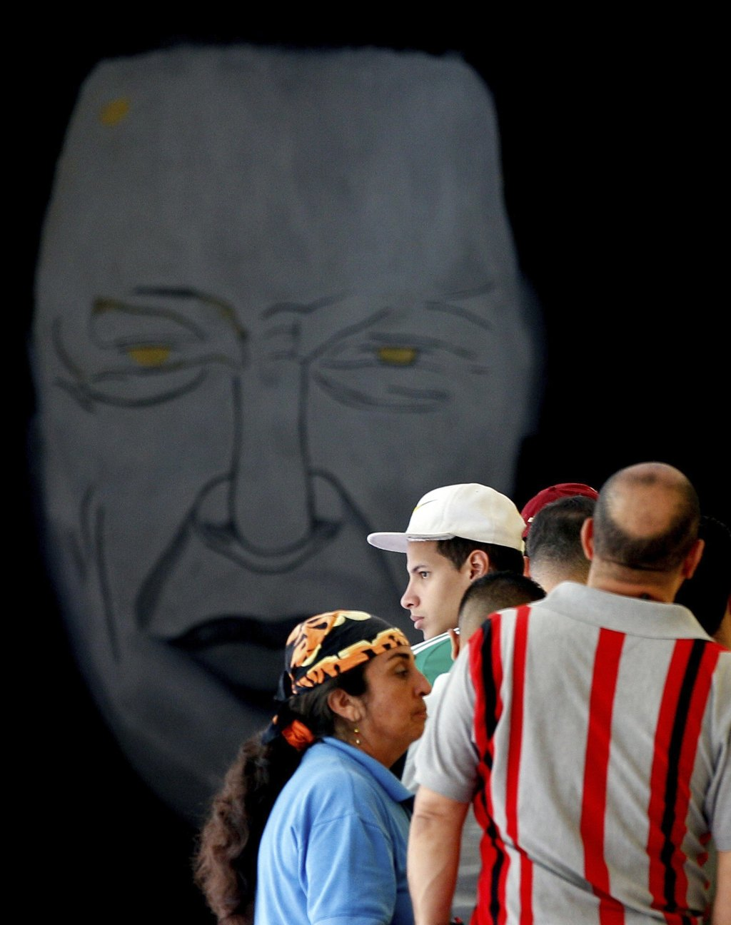 Voters line up to cast their ballots next to murals with images of late Venezuelan President Hugo Chavez, at a polling station in Caracas, Venezuela, ...