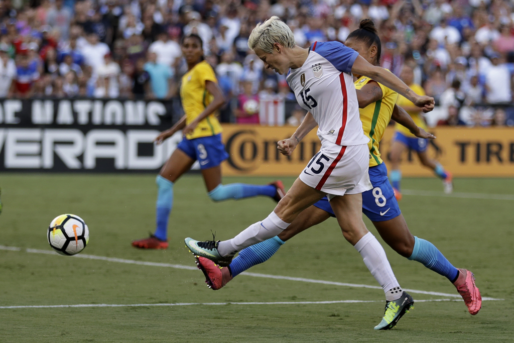 United States midfielder Megan Rapinoe (15) scores as Brazil midfielder Maria (8) defends during the second half of a Tournament of Nations women's so...