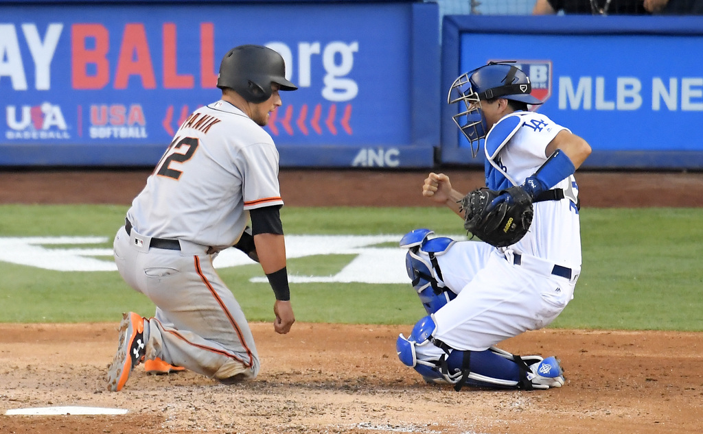 Los Angeles Dodgers catcher Austin Barnes, right, celebrates after tagging out San Francisco Giants' Joe Panik as Panik tried to score on a fly ball h...