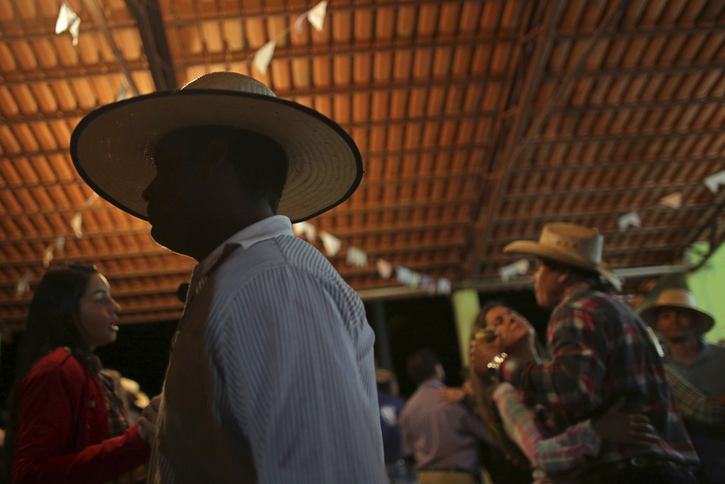 In this July 20, 2017 photo, cowboys dance during the ball at the camp, the night before the ascent to the Serra da Boa Vista, during the Ox Cart Fest...