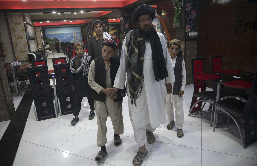 In this photo taken on Tuesday, July 25, 2017, Mohammed Naseer, with black turban, holds his sons' hand when they enter a Pizza Restaurant in Kabul, A...