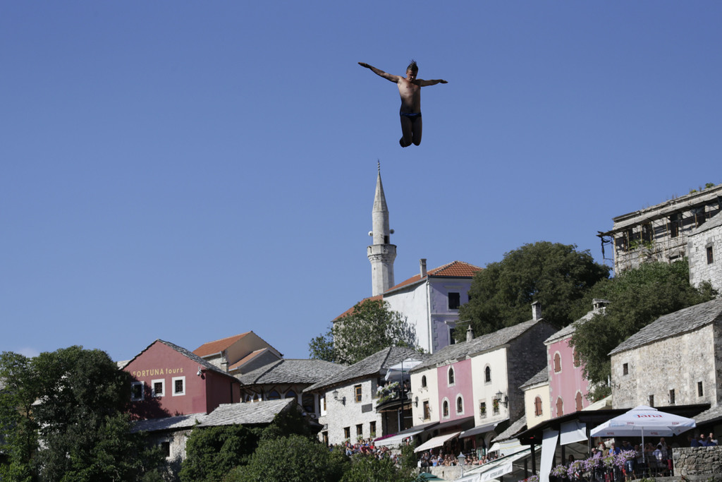 Spectators watch as a diver jumps from the Old Mostar Bridge during 451th traditional annual high diving competition, in Mostar, 140 kms south of Bosn...
