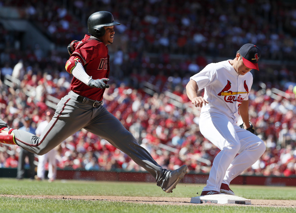 Arizona Diamondbacks' Ketel Marte, left, is out as St. Louis Cardinals relief pitcher Seung-Hwan Oh beats Marte to first during the eighth inning of a...