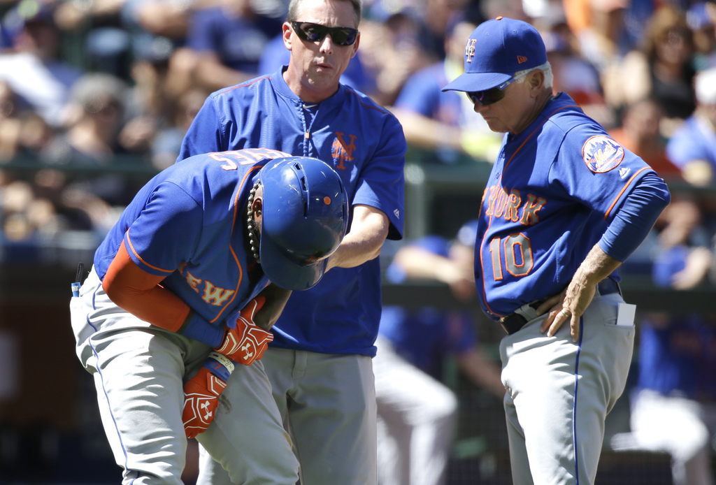 New York Mets' Jose Reyes, left, holds his arm as he stands with a trainer and manager Terry Collins, right, after he was hit by a pitch in the fifth ...