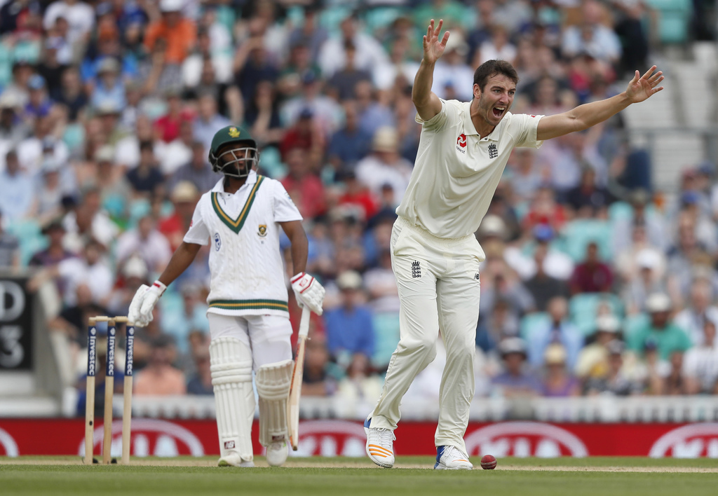 England's Toby Roland-Jones celebrates taking the wicket of South Africa's Temba Bavuma, left, on the fifth day of the third test match between Englan...