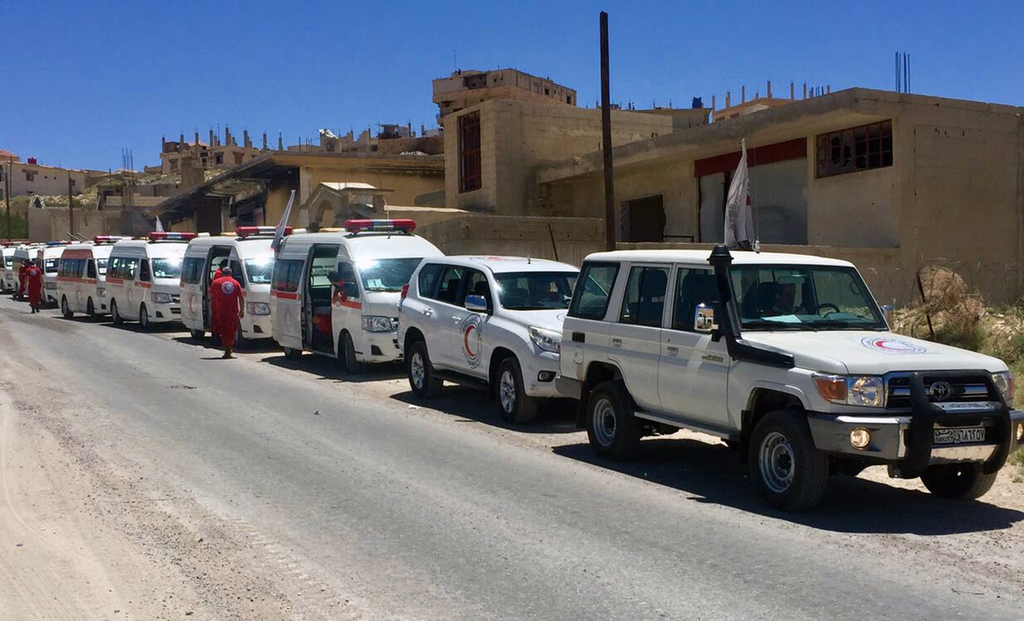 This Monday, July 31, 2017 photo released by the government-controlled Syrian Central Military Media, shows ambulances of the Syrian Arab Red Crescent...