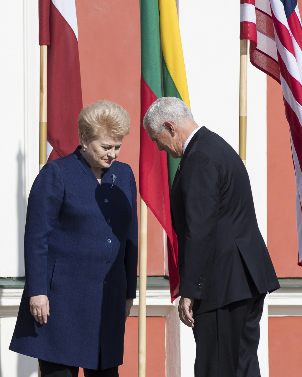 U.S. Vice President Mike Pence, right, and Lithuania's President Dalia Grybauskaite bow each other as they attend the official welcoming ceremony prio...