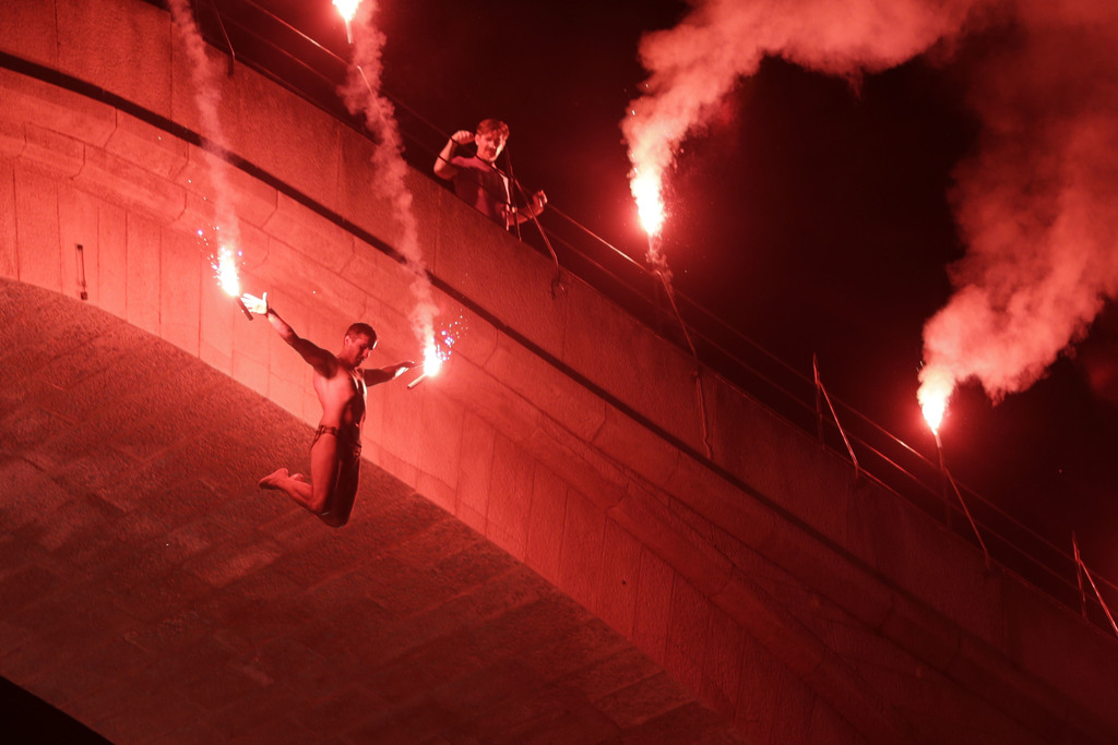 A Bosnian jumper, launches himself while holding burning torches, during traditional night jump from the Old Mostar Bridge, in Mostar, 140 kms south o...