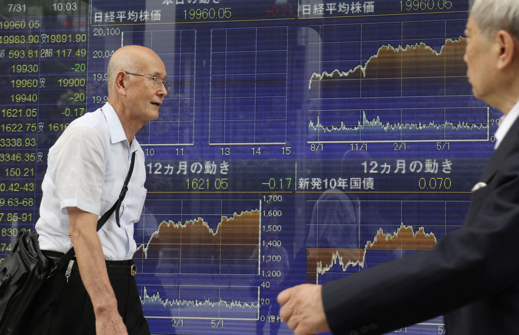 Men walk past an electronic stock indicator of a securities firm in Tokyo, Monday, July 31, 2017. Shares were mixed in Asia early Monday, with Chinese...