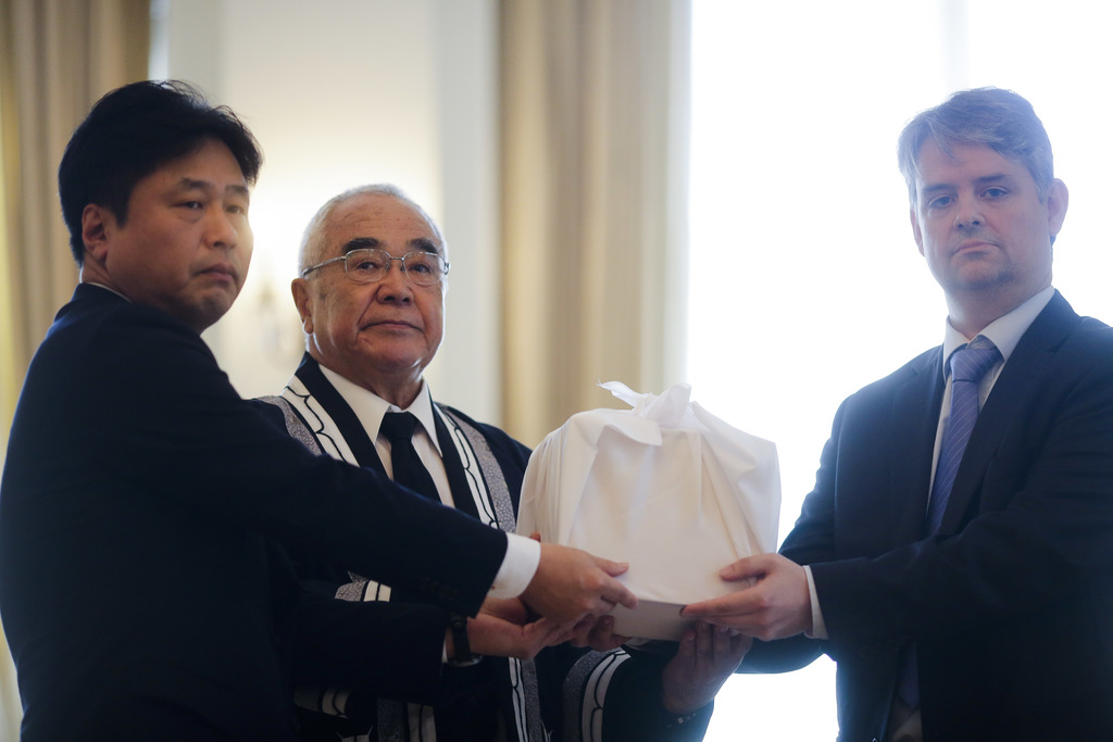 From right, Alexander Paschos chairman of the Berlin Society of Anthropology, Ethnology and Prehistory overhands a box with of a skull of Japan's Ainu...