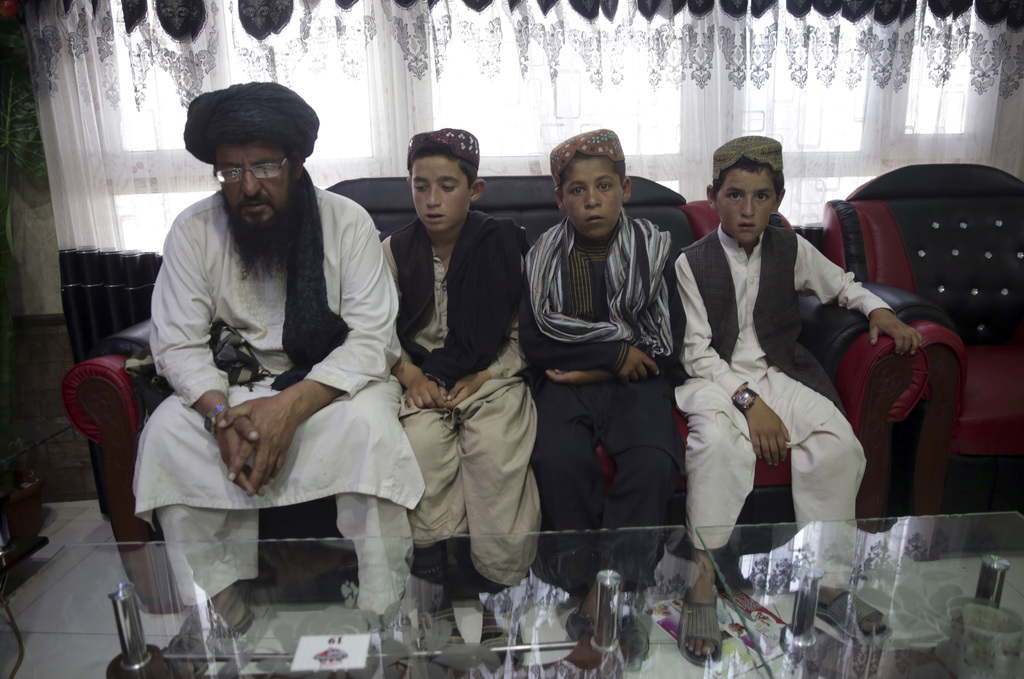 In this photo taken on Tuesday, July 25, 2017, Mohammed Naseer, with black turban, and three children wait for their food iN a Pizza Restaurant in Kab...