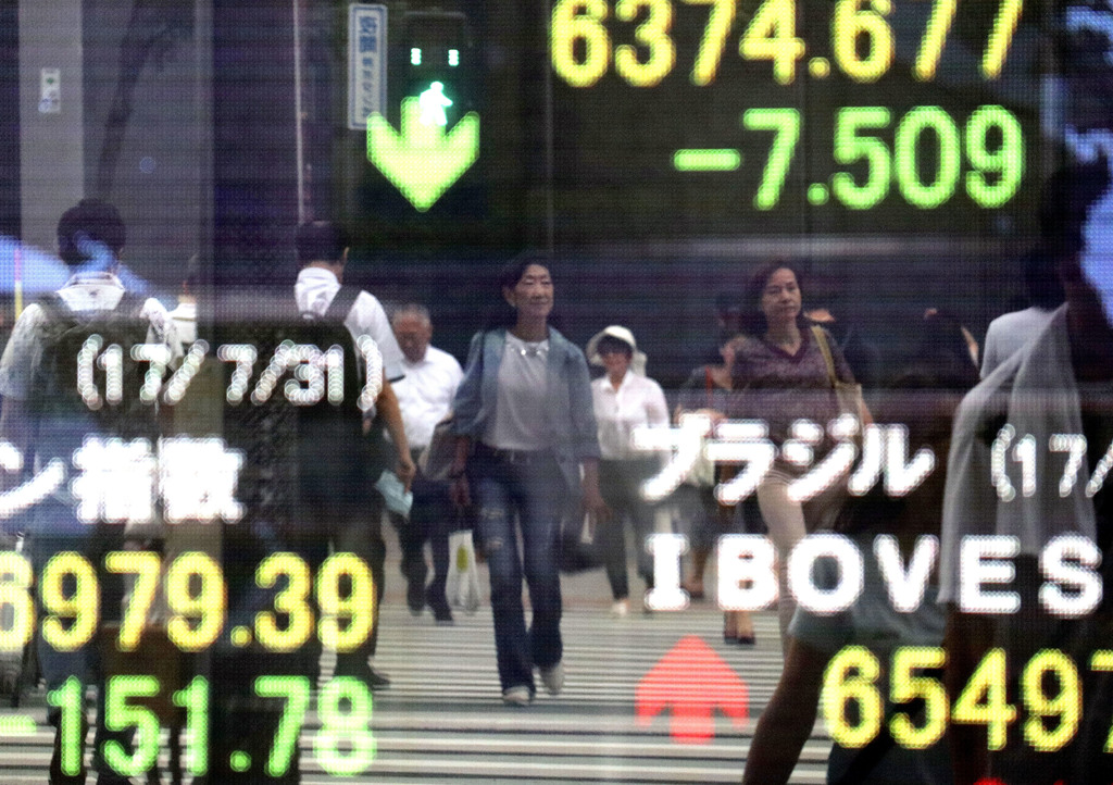 People are reflected on an electronic stock indicator of a securities firm in Tokyo, Monday, July 31, 2017. Shares were mixed in Asia early Monday, wi...