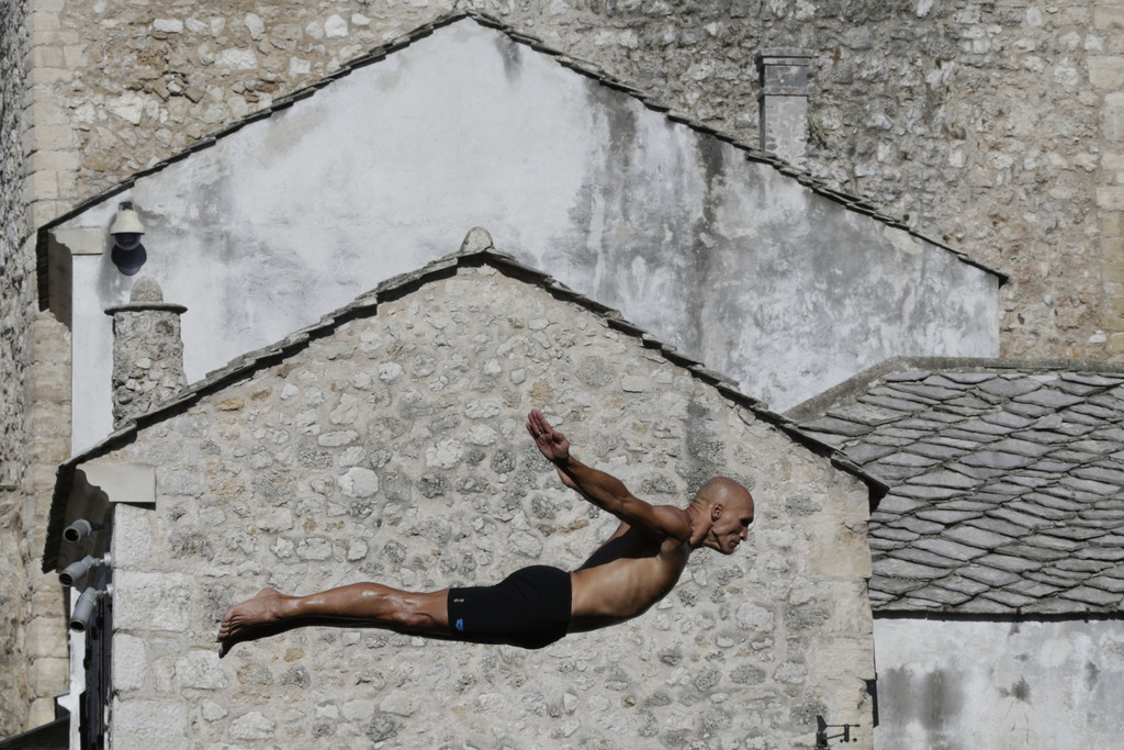 A diver drops through the air from the Mostar bridge during 451th traditional annual high diving competition, in Mostar, 140 kms south of Bosnian capi...