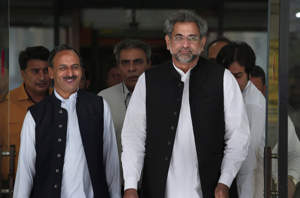 Pakistan's premier-designate Shahid Khaqan Abbasi, right, leaves with his aids after meeting with politicians in Parliament house in Islamabad, Pakist...