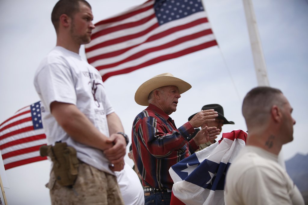 FILE - In this April 18, 2014, file photo, rancher Cliven Bundy, flanked by armed supporters, speaks at a protest camp near Bunkerville, Nev. U.S. Int...