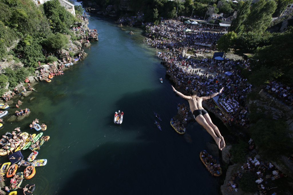 A diver drops through the air from the Mostar bridge during the 451th traditional annual high diving competition, in Mostar, 140 kms south of Bosnian ...