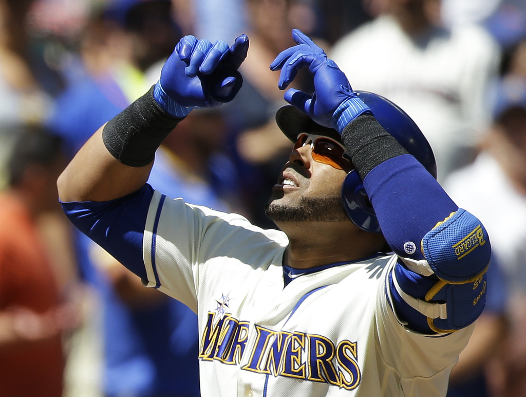 Seattle Mariners' Nelson Cruz looks up as he crosses the plate after he hit a three-run home run in the first inning of a baseball game against the Ne...