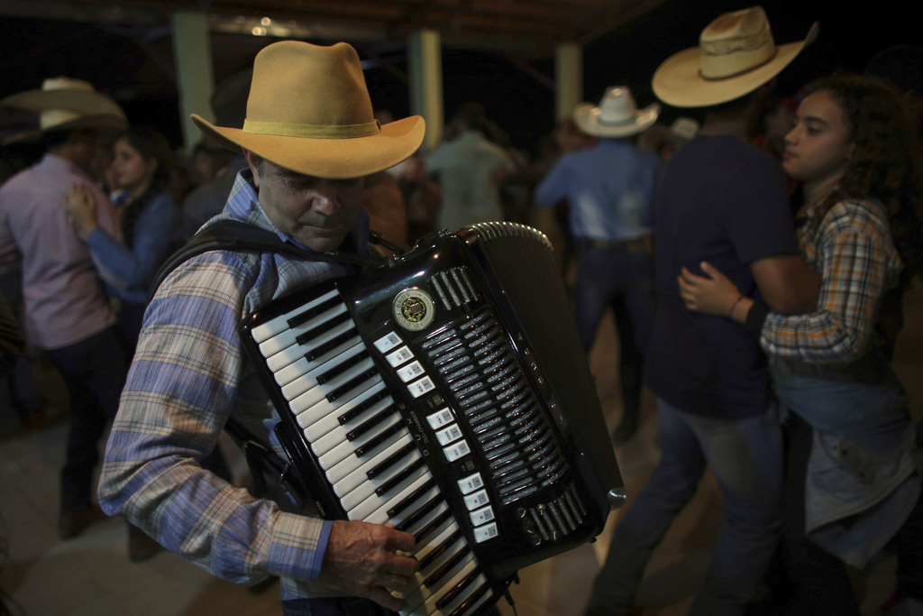 """In this July 20, 2017 photo, """"Dionisio of the Accordion,"""" plays during the dance at the camp, the night before the ascent to the Serra da Boa Vista, d..."""