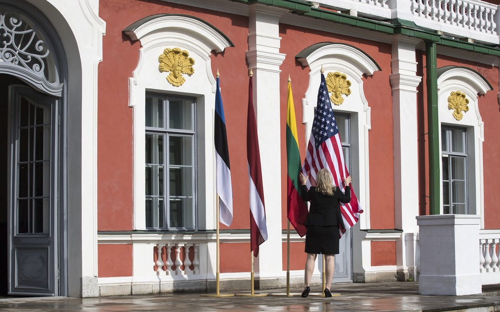 A protocol official sets a flag of the United States and flags of the Baltic states, from left, Estonia, Latvia and Lithuania, before the arrival of U...