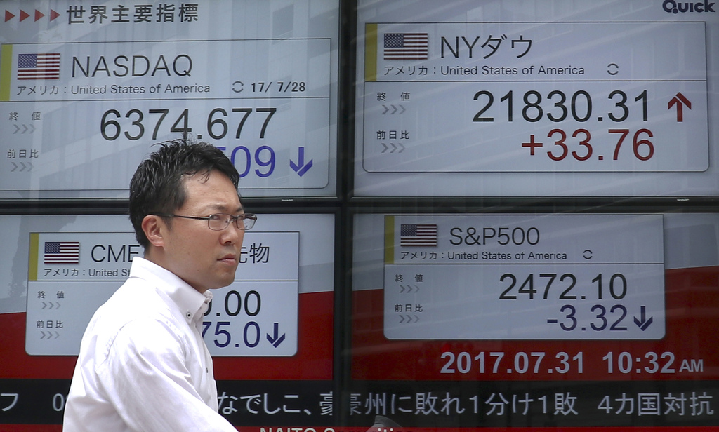 A man walks past an electronic stock indicator of a securities firm in Tokyo, Monday, July 31, 2017. Shares were mixed in Asia early Monday, with Chin...