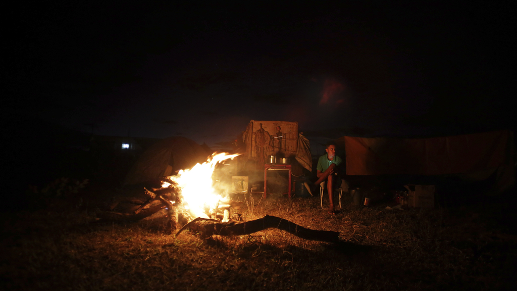 In this July 20, 2017 photo, a cowboy gets warm next to the camp fire, the night before the ascent to the Serra da Boa Vista, during the Ox Cart Festi...