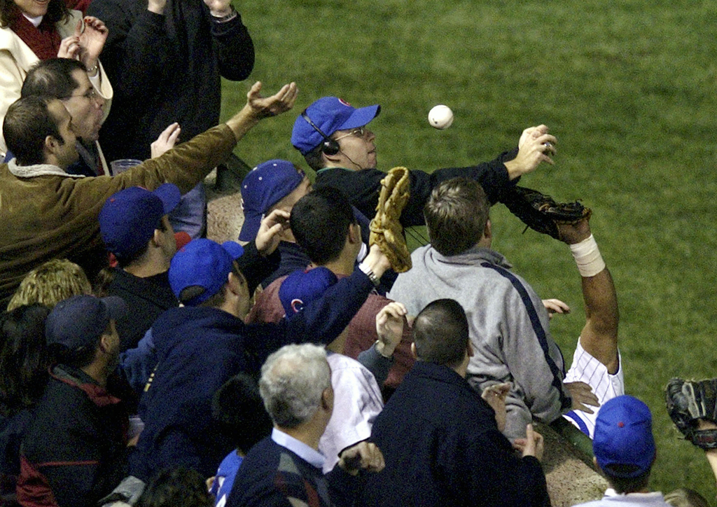 FILE - In this Oct 14, 2003, file photo, Steve Bartman, top center, catches a ball as Chicago Cubs left fielder Moises Alou's arm is seen reaching int...