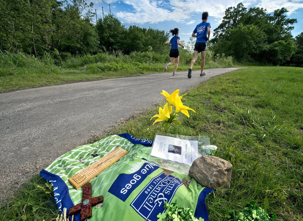 In a June 1, 2017 photo, runners pass by a memorial to homicide victim Mike Darby, as they headed west on the Indian Creek Trail near Wornall Road in ...