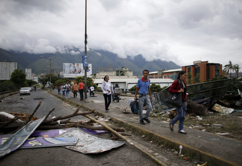 Pedestrians walk past a barricade made by anti-government demonstrators, in Caracas, Venezuela, Monday, July 31, 2017. Electoral authorities said more...