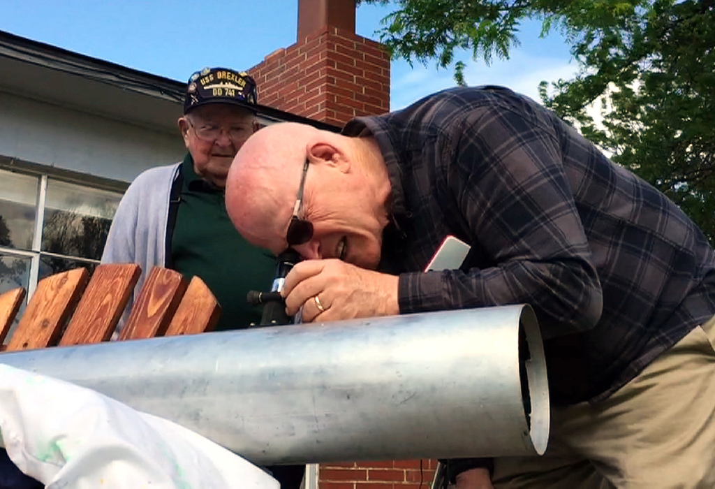 This frame grab from a video shows Gene Brick, 92, left, and his son, Bartt Brick, peering through a telescope in Madras, Ore., June 12, 2017, that th...