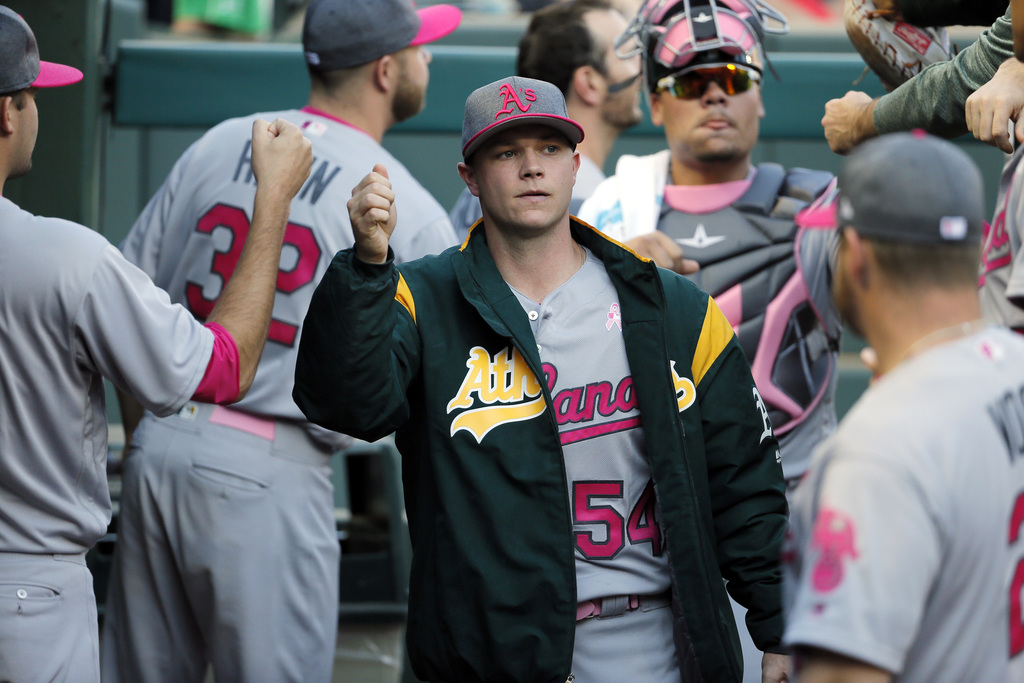 FILE - In this May 13, 2017, file photo, Oakland Athletics starting pitcher Sonny Gray, center, is greeted in the dugout before the team's baseball ga...
