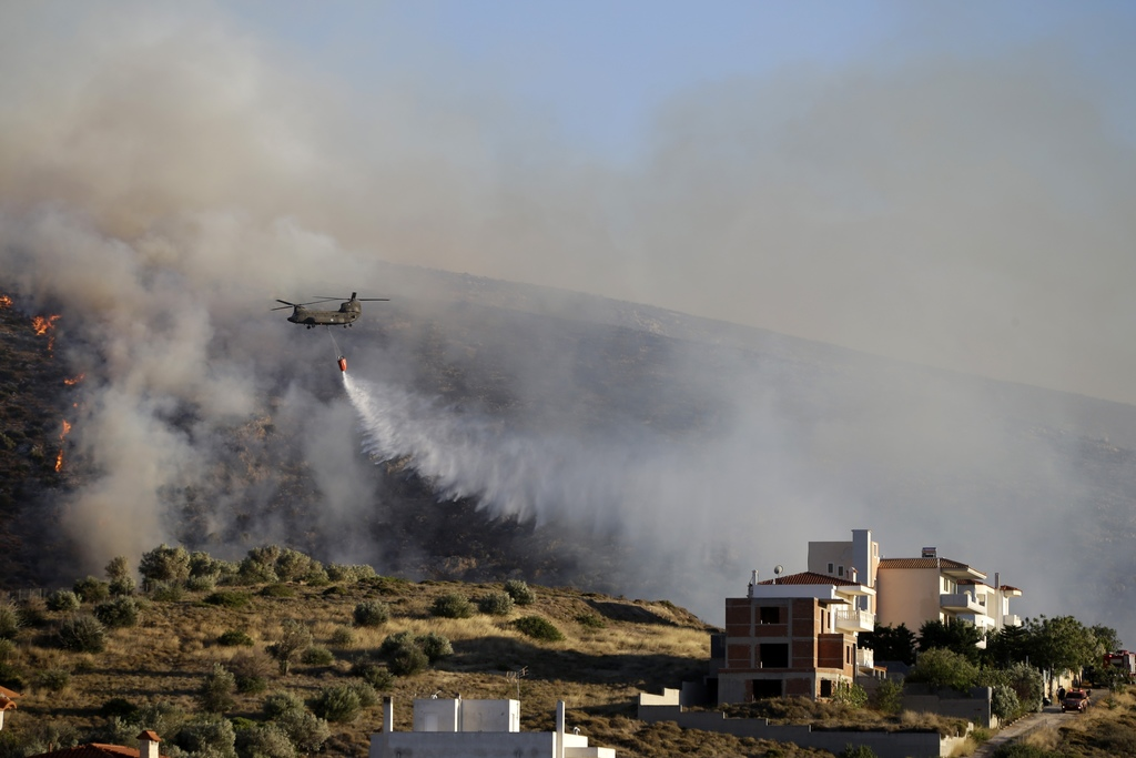An helicopter drops water over a fire in the Kalyvia area some 30 kilometers (18 miles) south of Athens, Monday, July 31, 2017. Dozens of firefighters...