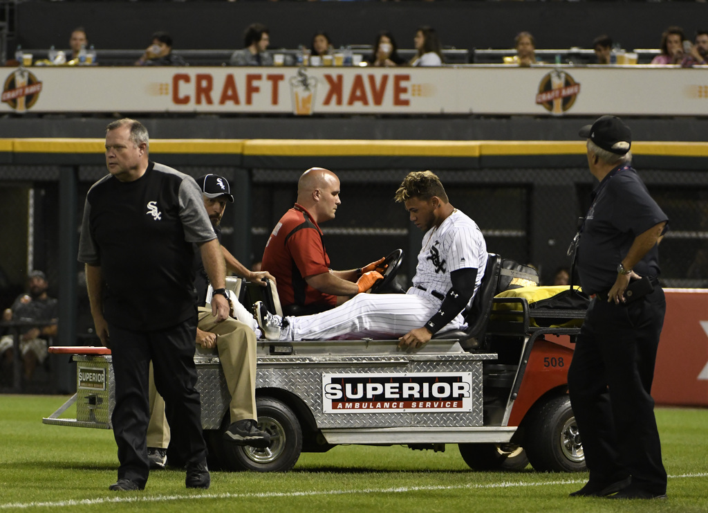 Chicago White Sox second baseman Yoan Moncada, center, is carted off the field after colliding with right fielder Willy Garcia on a double hit by Toro...