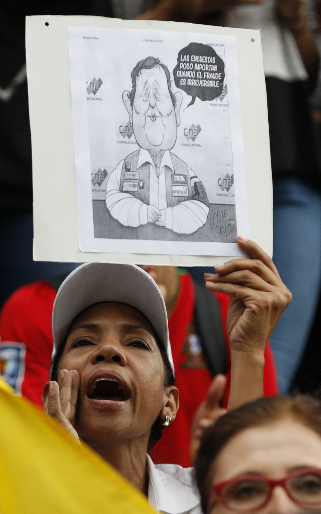 "An anti-government demonstrator holds a cartoon of the president of the National Electoral Center, Tibisay Lucena, that reads in Spanish ""The polls do..."