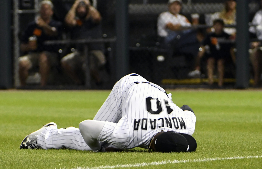 Chicago White Sox second baseman Yoan Moncada (10) lies on the ground after being hurt while trying to catch a double hit by Toronto Blue Jays' Darwin...