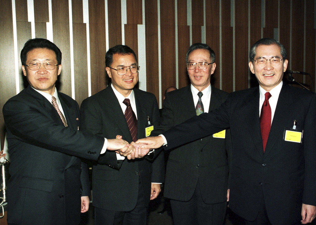 n this April 24, 1999 file photo, delegates of the North and South Korea peace talks join hands before their meeting in Geneva, Switzerland, in this A...