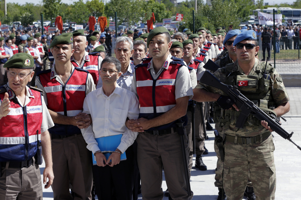 Paramilitary police and members of the special forces escort Kemal Batmaz, foreground centre, and Akin Ozturk, former Air Force commander, second row,...