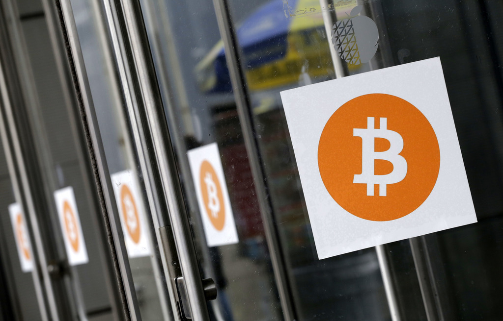 FILE - In this April 7, 2014, file photo, Bitcoin logos are displayed at the Inside Bitcoins conference and trade show in New York. The threat of a sp...