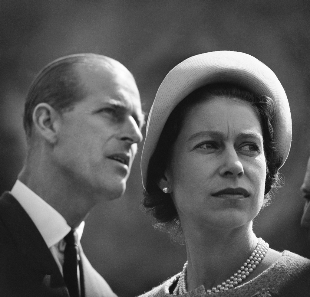 FILE - In this June 20, 1959 file photo Queen Elizabeth II and Prince Philip are pictured in Schefferville, as they listen to explanation on workings ...