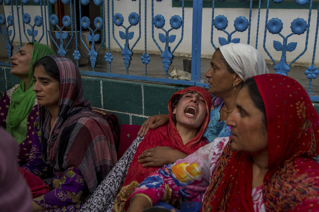 An unidentified relative comforts the wailing sister of a Kashmiri civilian who was killed during protest near the site of gun battle at her residence...