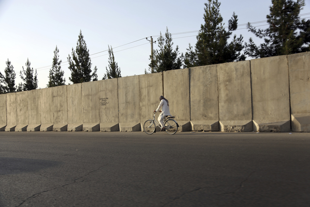 In this Monday, July 31, 2017 photo, an Afghan man ride his bicycle walks past blast walls in Kabul, Afghanistan. A U.S. watchdog says unprecedented s...