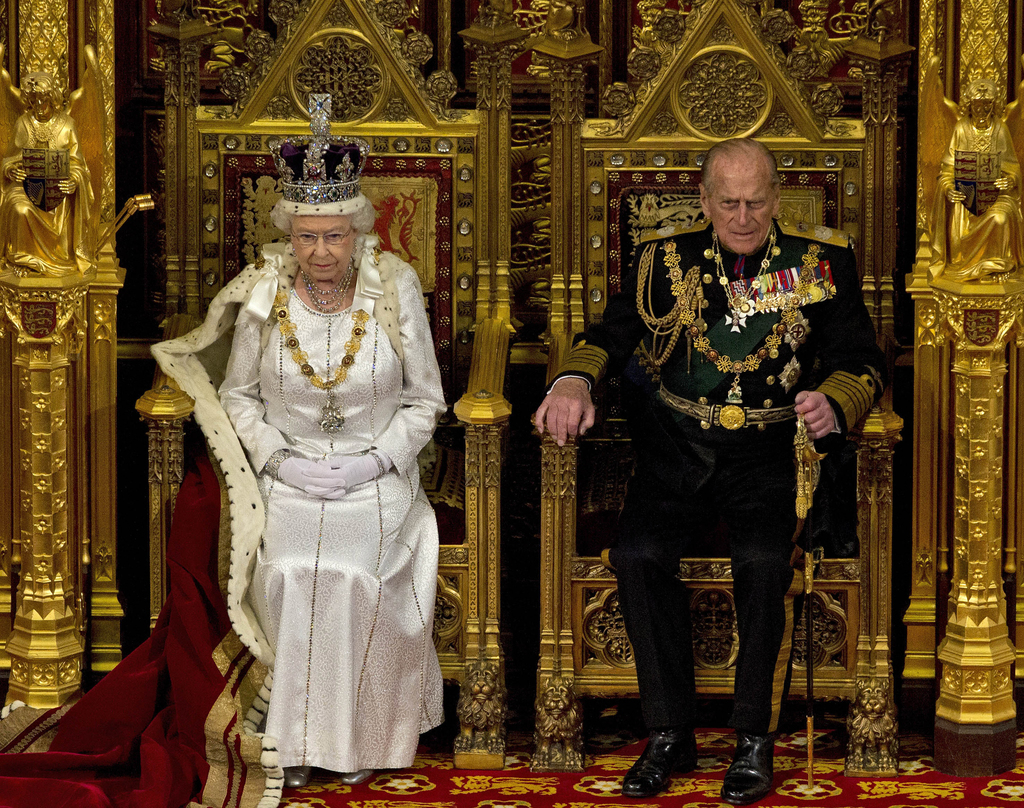 FILE - In this Wednesday, May 9, 2012 file photo Britain's Queen Elizabeth II sits next to Prince Philip in the House of Lords as she waits to read th...