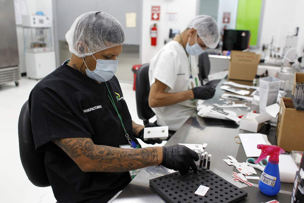In this Monday, July 24, 2017 photo, two Natural Ventures production workers pack cannabis paraphernalia in Caguas, Puerto Rico. Investors in Puerto R...