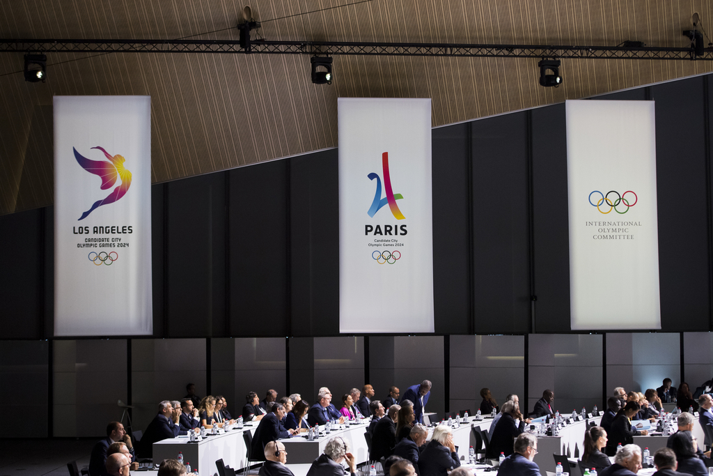 FILE - This July 11, 2017 file photo shows banners of Los Angeles 2024 candidacy, Paris 2024 candidacy and the International Olympic Committee (IOC), ...